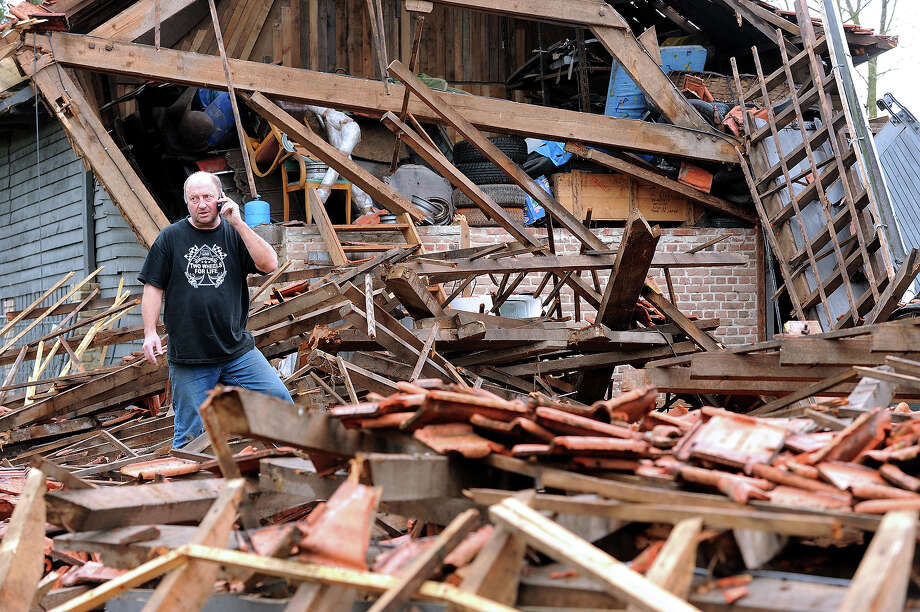 An inhabitant looks at on October 21, 2013 damages after a mini-tornado ripped on the eve in Steent'je, near the French northern city of Bailleul. Two persons were injured. Photo: PHILIPPE HUGUEN, AFP/Getty Images / 2013 AFP