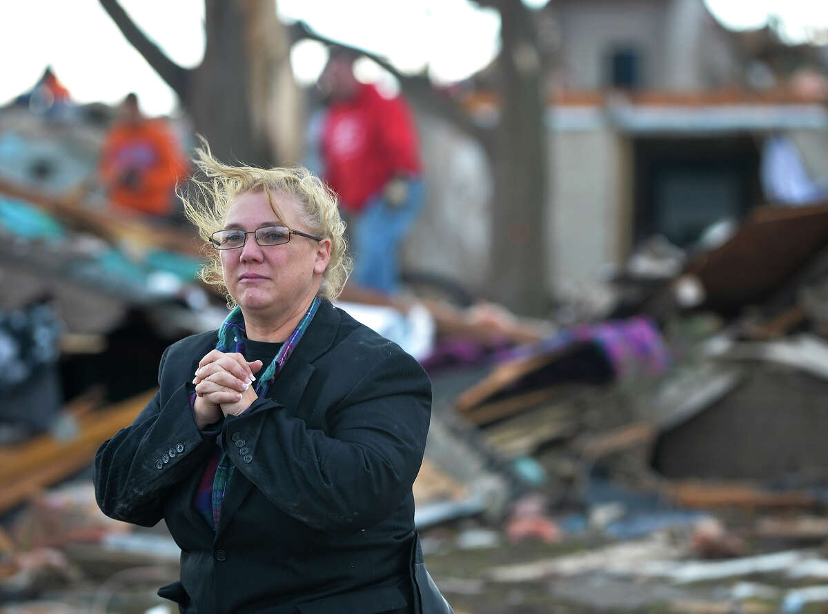 A resident of Washington, Ill., surveys the damage to her home and neighbors after a tornado and severe thunderstorms swept through a portion of the town on Sunday, Oct. 17, 2013.