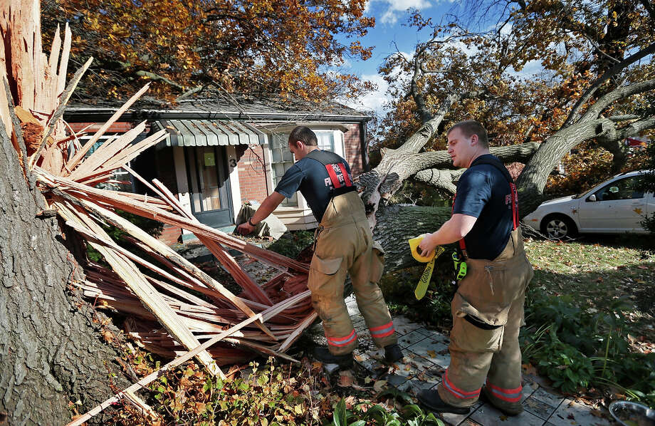 Webster Groves firefighters Chris Manita, center, and Matt Grossenhieder climb over a tree that fell on a house on Clydehurst Drive in Webster Groves, Mo., Sunday, Nov. 17, 2013.  The residents of the house were home at the time the tree fell but were not injured. Intense thunderstorms and tornadoes swept across a number of Midwestern states Sunday, causing damage in several central Illinois communities while sending people to their basements for shelter and even prompting officials at Soldier Field in Chicago to evacuate the stands and delay the Bears game. Photo: David Carson, ASSOCIATED PRESS / AP2013