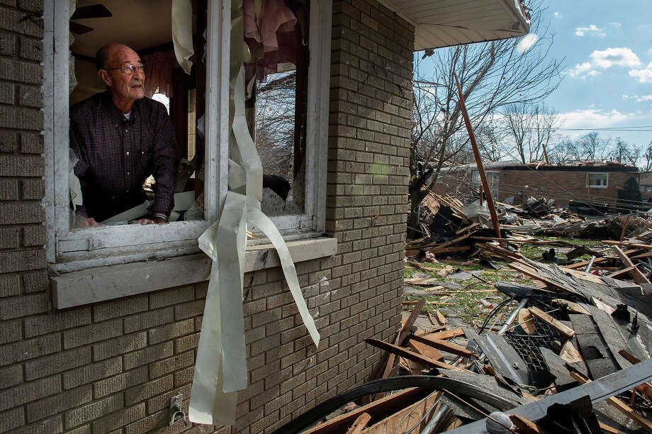 Chuck Phillips looks out at the destruction that tore off part of his roof and left houses around him destroyed after a tornado left a path of devastation through the north end of Pekin, Il.,Sunday, Nov. 17, 2013. Intense thunderstorms and tornadoes swept across the Midwest on Sunday, causing extensive damage in several central Illinois communities while sending people to their basements for shelter. Photo: FRED ZWICKY, ASSOCIATED PRESS / ALL RIGHTS RESERVED2013