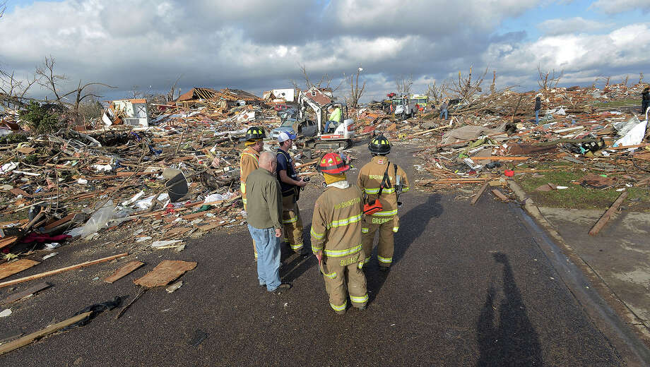 Washington, Ill., firefighters stand in the middle of Devonshire Street on the North side of Washington, Ill., after a tornado leveled at least fifty homes, Sunday, Nov. 17, 2013. High winds that followed the tornado are causing danger as homeowners and emergency workers try to search homes. Photo: Steve Smedley, ASSOCIATED PRESS / AP2013