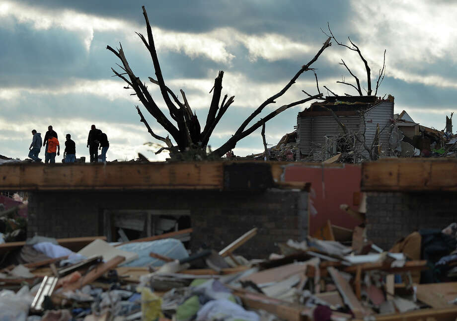 Residents search through a neighborhood in Washington, Ill., after a tornado and strong thunderstorms  swept through the north part of the town destroying several homes on Sunday, Nov. 17, 2013. Photo: Ron Johnson, AP / Journal Star