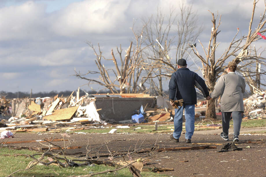 A couple walks down a street in the Devonshire subdivision on the North side of Washington, Ill., Sunday, Nov. 17, 2013. Intense thunderstorms and tornadoes swept across the Midwest, causing extensive damage in several central Illinois communities while sending people to their basements for shelter. Photo: Steve Smedley, AP / The Pantagraph