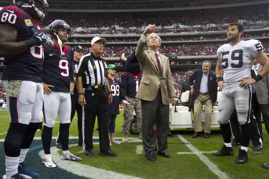 Former President George W. Bush, center, with his father, George H.W. Bush, standing in the background, flips the coin before the Texans game against the Raiders. Photo: Brett Coomer, Houston Chronicle