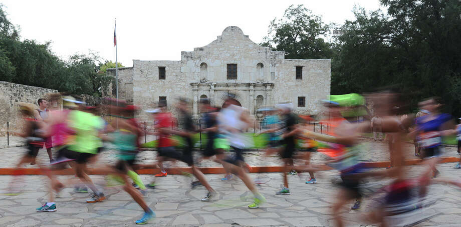 Runners in the Rock 'n' Roll San Antonio Marathon & 1/2 Marathon pass through Alamo Plaza. About 26,000 runners competed, and thousands of supporters and spectators watched them along the 26.2-mile route. Photo: Jerry Lara / San Antonio Express-News