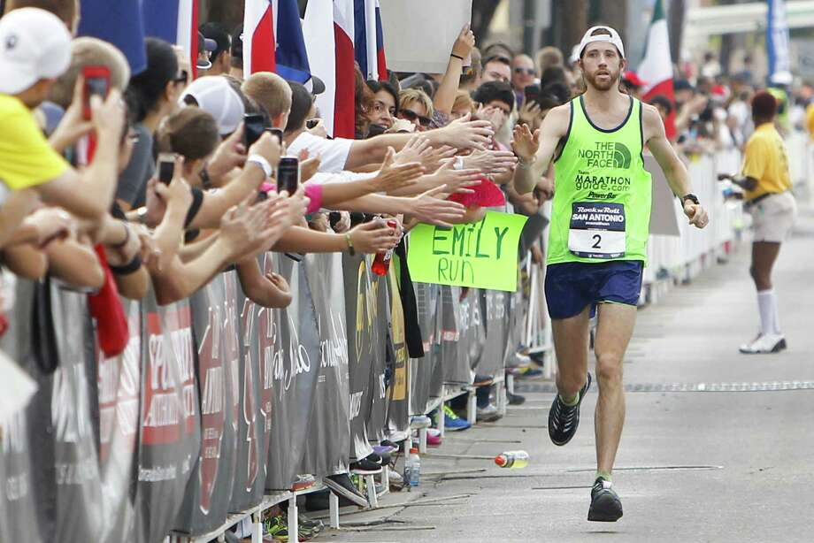 Fans greet men's winner Michael Wardian as he approaches the finish line in San Antonio. He flew to Las Vegas to race in another marathon, finishing third there late Sunday. Photo: Marvin Pfeiffer / San Antonio Express-News