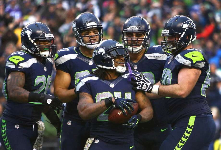 Seattle Seahawks player Marshawn Lynch is surrounded by teammates after a fourth quarter touchdown against the Minnesota Vikings on Sunday, November 17, 2013 at CenturyLink Field in Seattle. Photo: JOSHUA TRUJILLO, SEATTLEPI.COM