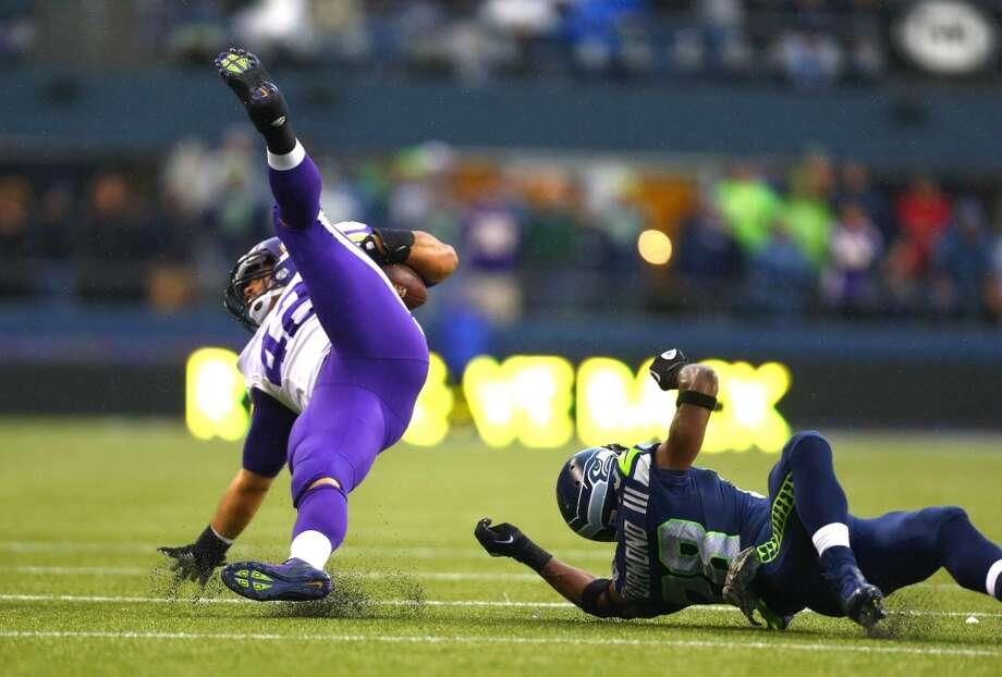 Minnesota Vikings player Jerome Felton is upended by Seahawks player Walter Thurmond. Photo: JOSHUA TRUJILLO, SEATTLEPI.COM
