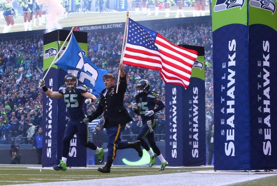 Congressional Medal of Honor recipient Leroy Petry and Seattle Seahawks player Heath Farwell lead the team out of the tunnel before a game against the Minnesota Vikings. Photo: JOSHUA TRUJILLO, SEATTLEPI.COM