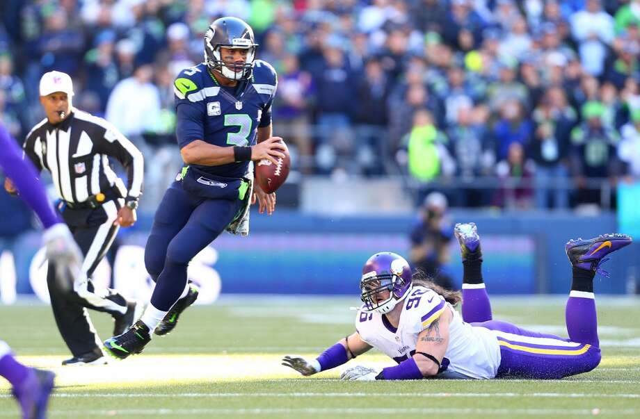 Seattle Seahawks quarterback Russell Wilson evades  Minnesota Vikings player Brian Robinson. Photo: JOSHUA TRUJILLO, SEATTLEPI.COM