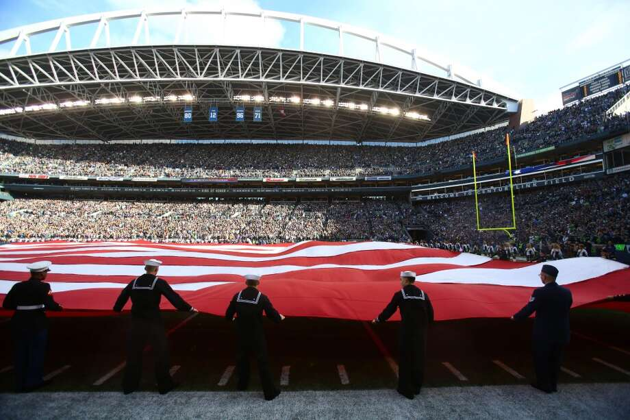 Military members unfurl a nearly 100 yard long flag before a game between the Seattle Seahawks and Minnesota Vikings. Photo: JOSHUA TRUJILLO, SEATTLEPI.COM