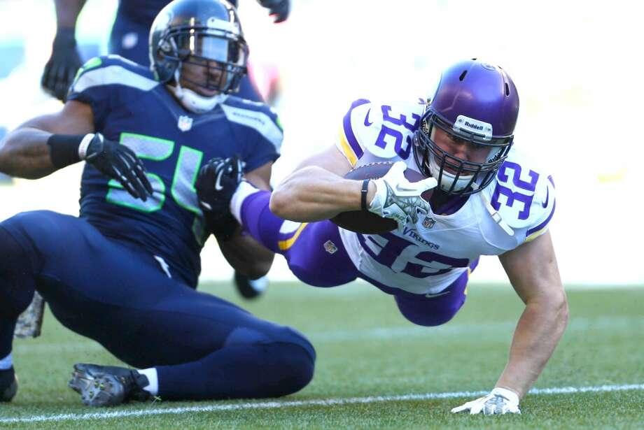Minnesota Vikings player Toby Gerhart (32) is taken down by Seattle Seahawks player Bobby Wagner. Photo: JOSHUA TRUJILLO, SEATTLEPI.COM