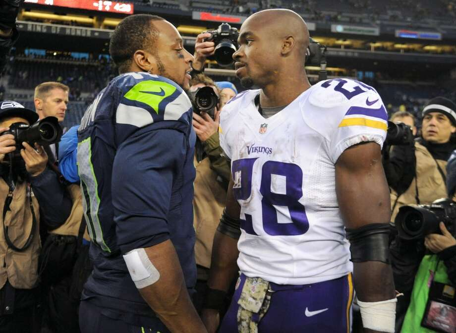 Wide receiver Percy Harvin (11) of the Seattle Seahawks and running back Adrian Peterson (28) of the Minnesota Vikings speak after the game at CenturyLink Field on November 17, 2013. Photo: Steve Dykes, Getty Images