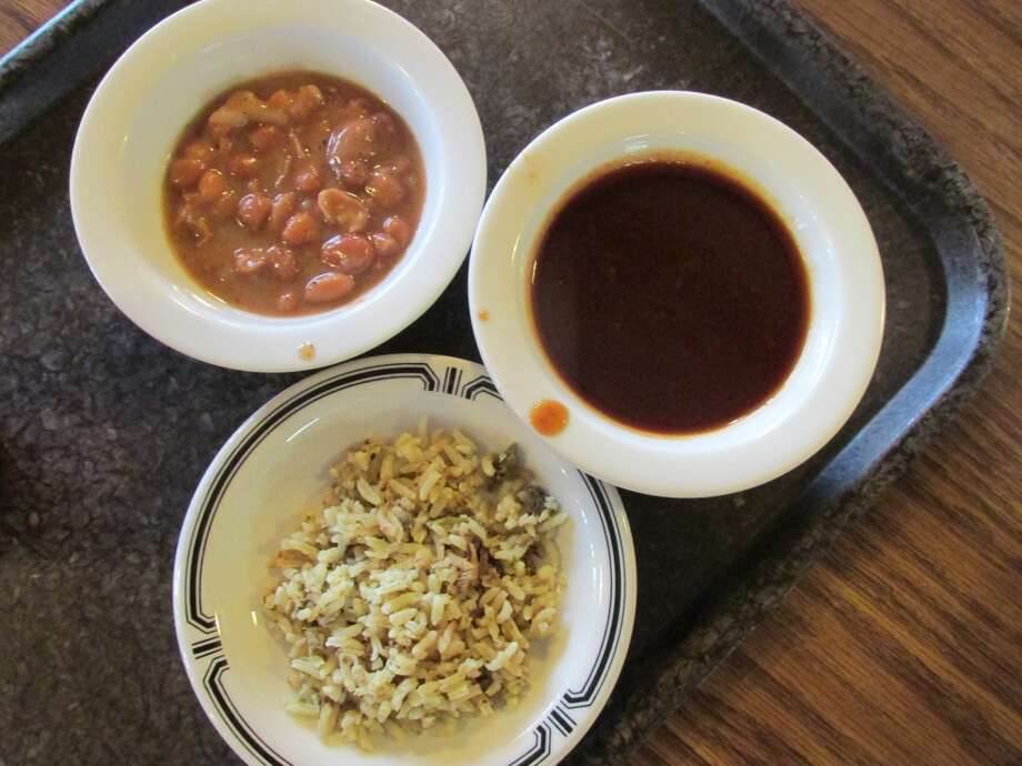 Sides of dirty rice, beans and barbecue sauce at JB's Barbecue in Orange. Photo: Cat5