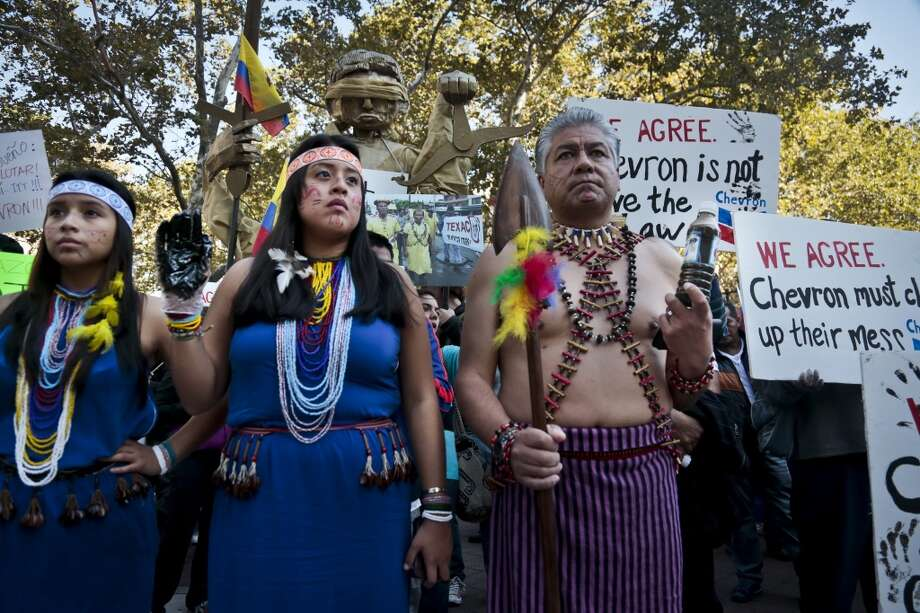"""Protestors rally outside a federal court in New York to protest oil giant Chevron's """"racketeering lawsuit against the Ecuadorian rainforest villagers,"""" according to a statement from environmental group Amazon Watch, Tuesday, Oct. 15, 2013.  The group says the lawsuit is """"retaliatory"""" after plaintiffs, including rainforest villagers participating in the rally,  """"won a landmark judgement against Chevron in an Ecuadorian court in 2011 in which the company was ordered to pay $18 billion"""" for rainforest pollution.   (AP Photo/Bebeto Matthews) Photo: AP"""