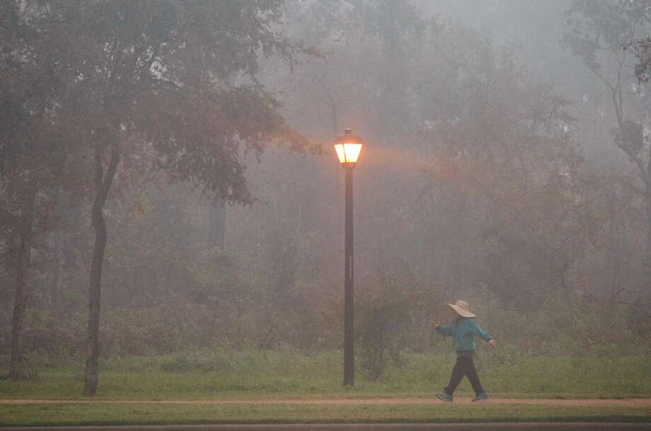 Thi Nguyen does her daily walk around Memorial Park on a foggy Monday morning. Photo: Johnny Hanson, Houston Chronicle