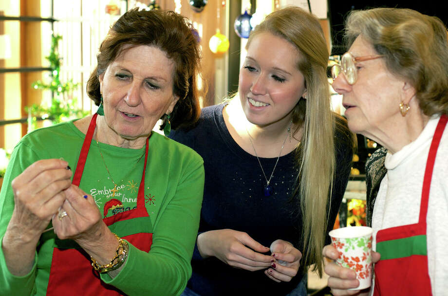 A glass ornament created by Scott Hallam of Shape Shifter Glass is admired by, from left to right, Teddy Marici, event co-chairwoman; Shape Shifter's Jess Mudd of Morrisville, N.C.; and Holy Trinity volunteer Helen Tomcsanyi during Holy Trinity Parish's annual Christmas fair and marketplace in Sherman. Nov. 15-16, 2013 Photo: Trish Haldin / The News-Times Freelance