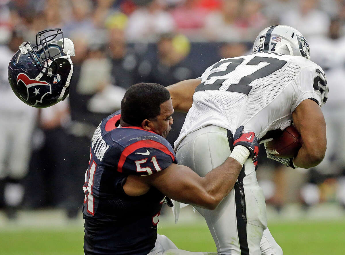 Houston Texans' Darryl Sharpton loses his helmet as he tackles Oakland Raiders' Rashad Jennings during the first half of an NFL football game Sunday, Nov. 17, 2013, in Houston.