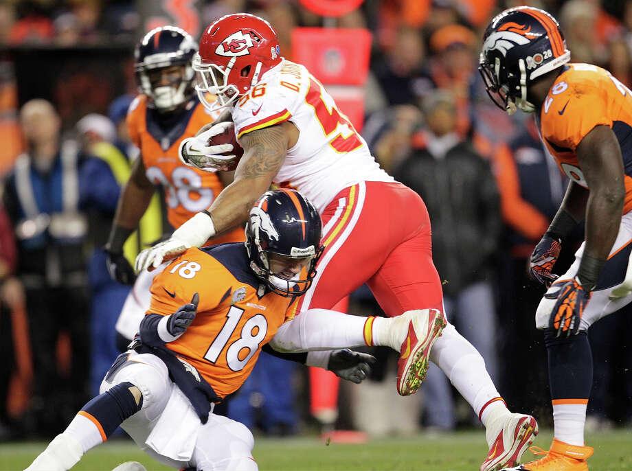 Denver Broncos quarterback Peyton Manning (18) hits Kansas City Chiefs inside linebacker Derrick Johnson (56) low after Johnson recovered a fumble in the first quarter of an NFL football game, Sunday, Nov. 17, 2013, in Denver. Photo: Joe Mahoney, ASSOCIATED PRESS / AP2013