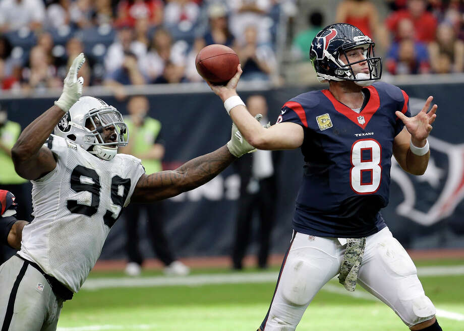 Houston Texans' Matt Schaub throws while being rushed by Oakland Raiders' Lamarr Houston (99) during the second half of an NFL football game Sunday, Nov. 17, 2013, in Houston. Photo: Morry Gash, AP / AP