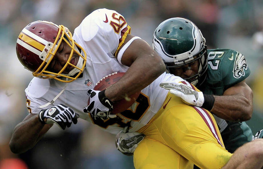 Washington Redskins running back Alfred Morris, left, is stopped by Philadelphia Eagles strong safety Nate Allen during the first half of an NFL football game in Philadelphia, Sunday, Nov. 17, 2013. Photo: Michael Perez, AP / FR168006 AP