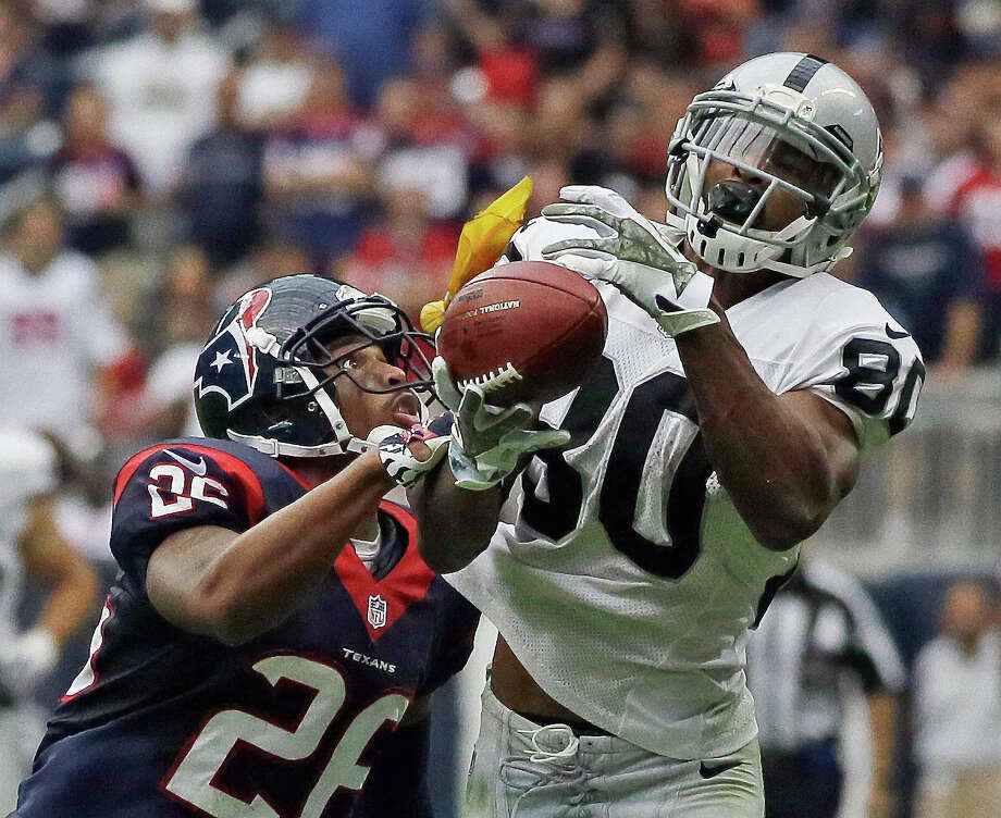 Houston Texans' Brandon Harris (26) is called for pass interference as Oakland Raiders' Rod Streater (80) catches a pass during the second half of an NFL football game Sunday, Nov. 17, 2013, in Houston. Photo: Tony Gutierrez, ASSOCIATED PRESS / AP2013