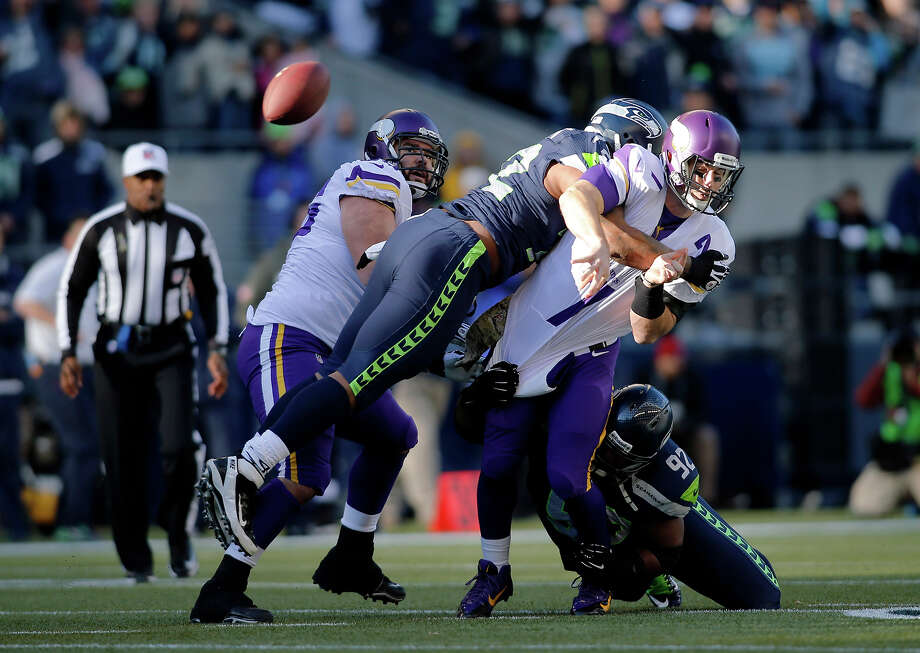 Minnesota Vikings quarterback Christian Ponder, right, is hit by Seattle Seahawks' Michael Bennett, second from left, and Brandon Mebane (92), right, as he attempts a pass in the first half of an NFL football game Sunday, Nov. 17, 2013, in Seattle. The Seahawks won 41-20. Photo: John Froschauer, ASSOCIATED PRESS / AP2013