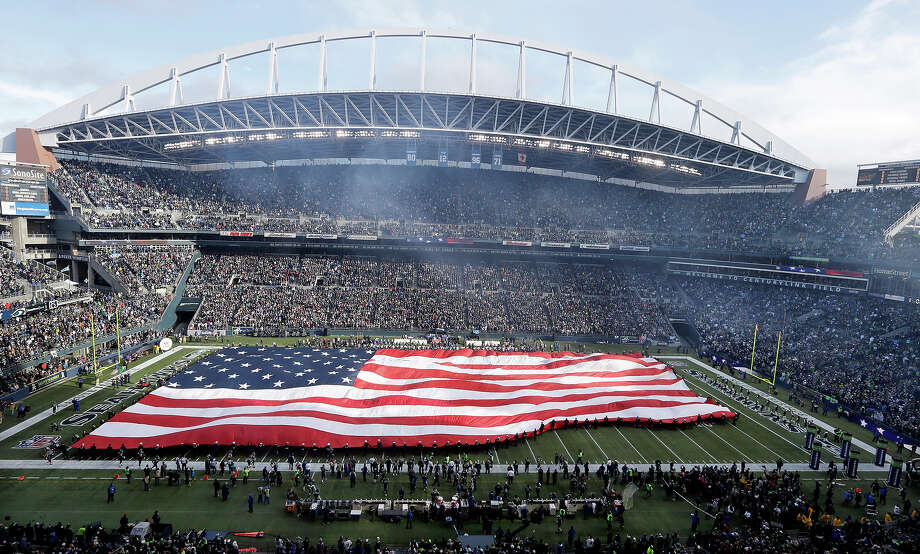 "A U.S. flag is unfurled at CenturyLink Field before an NFL football game between the Seattle Seahawks and Minnesota Vikings, Sunday, Nov. 17, 2013, in Seattle. The Seahawks honored members of the military as part of NFL's ""Salute to Service."" Photo: Rachel La Corte, AP / AP"