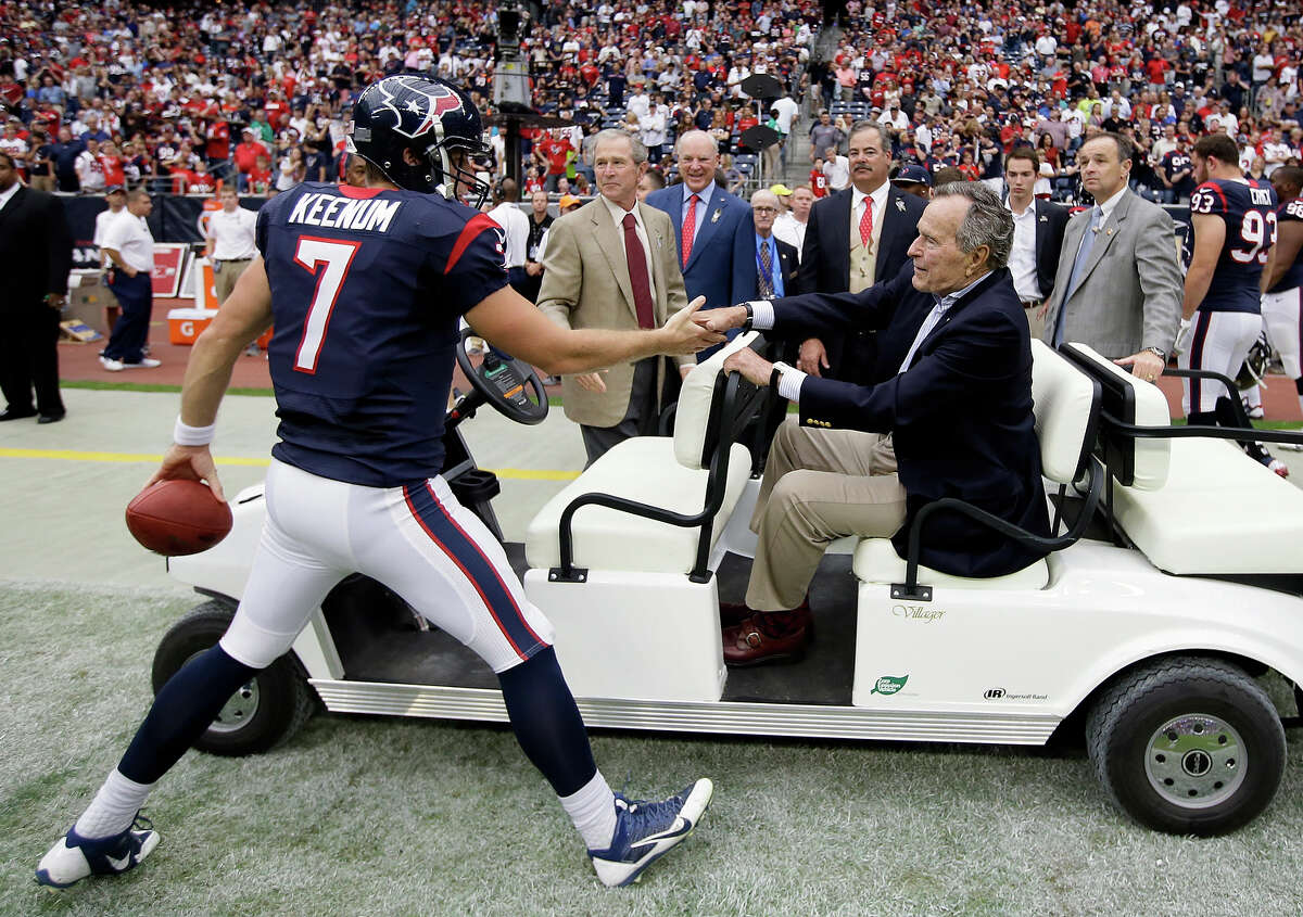 Houston Texans' Case Keenum shakes hands with former Presidents George H.W. Bush and George W. Bush before an NFL football game against the Oakland Raiders Sunday, Nov. 17, 2013, in Houston.