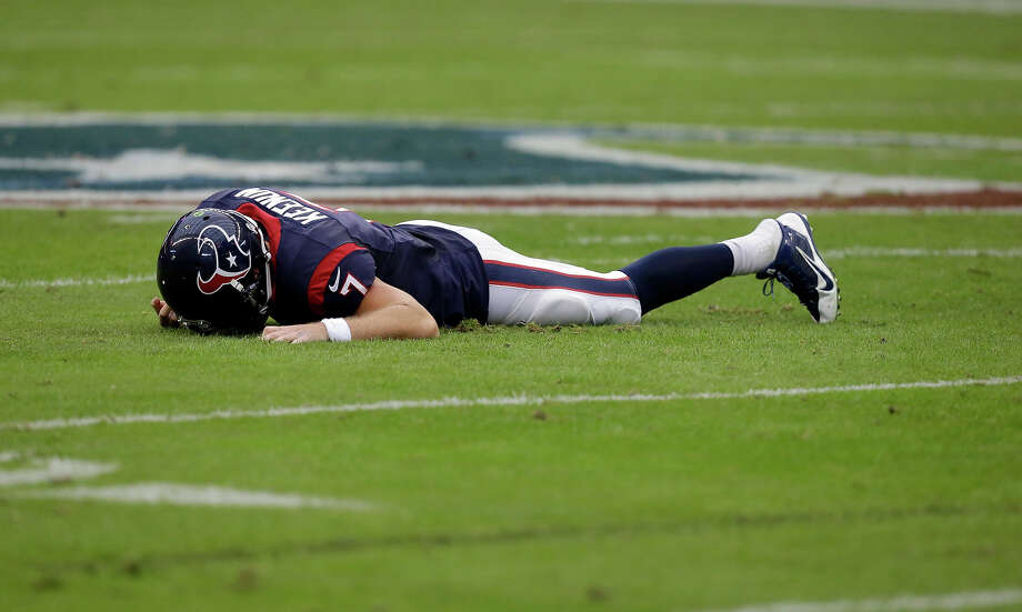 Houston Texans quarterback Case Keenum lays on the ground after being sacked by Oakland Raiders' Lamarr Houston during the first half of an NFL football game Sunday, Nov. 17, 2013, in Houston. Photo: Patric Schneider, ASSOCIATED PRESS / AP2013