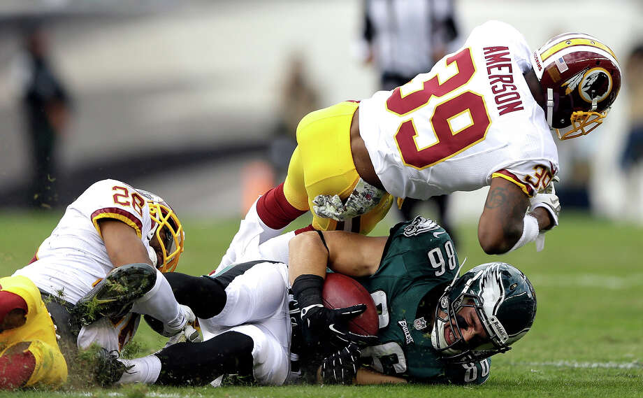 Philadelphia Eagles tight end Zach Ertz (86) is tackled by Washington Redskins cornerback Josh Wilson, left, and free safety David Amerson (39) during the first half of an NFL football game in Philadelphia, Sunday, Nov. 17, 2013. Photo: Matt Rourke, AP / AP