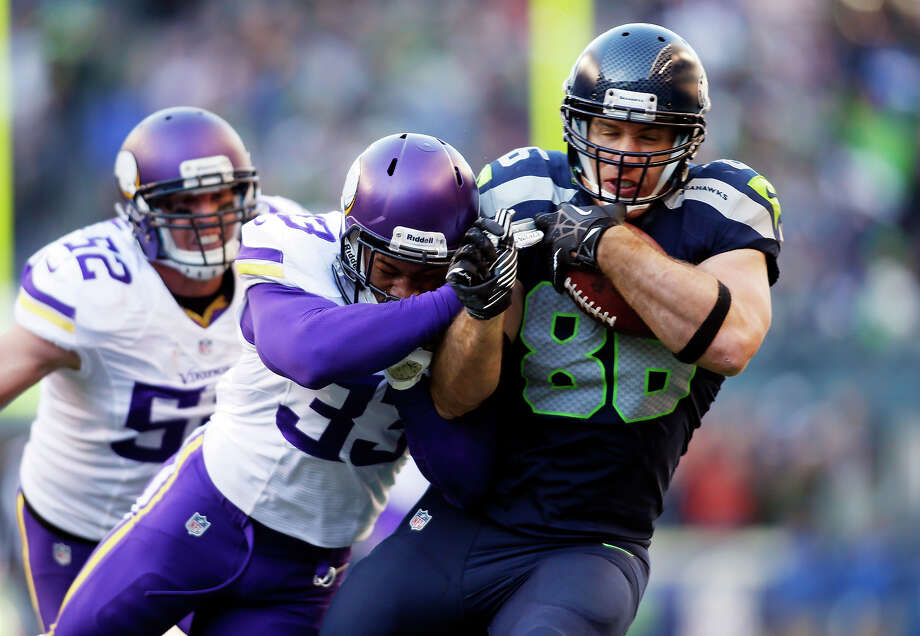 Seattle Seahawks' Zach Miller, right, is hit by Minnesota Vikings' Jamarca Sanford, center, as Chad Greenway follows in the first half of an NFL football game Sunday, Nov. 17, 2013, in Seattle. Photo: JOHN FROSCHAUER, ASSOCIATED PRESS / AP2013