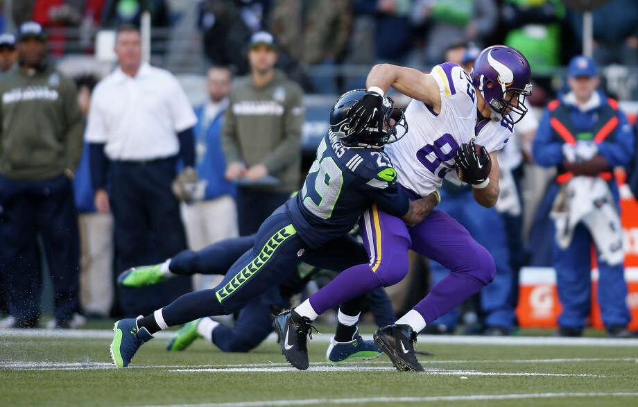 Minnesota Vikings' John Carlson carries the ball and is hit by Seattle Seahawks' Earl Thomas in the first half of an NFL football game, Sunday, Nov. 17, 2013, in Seattle. Photo: John Froschauer, AP / FR74207 AP