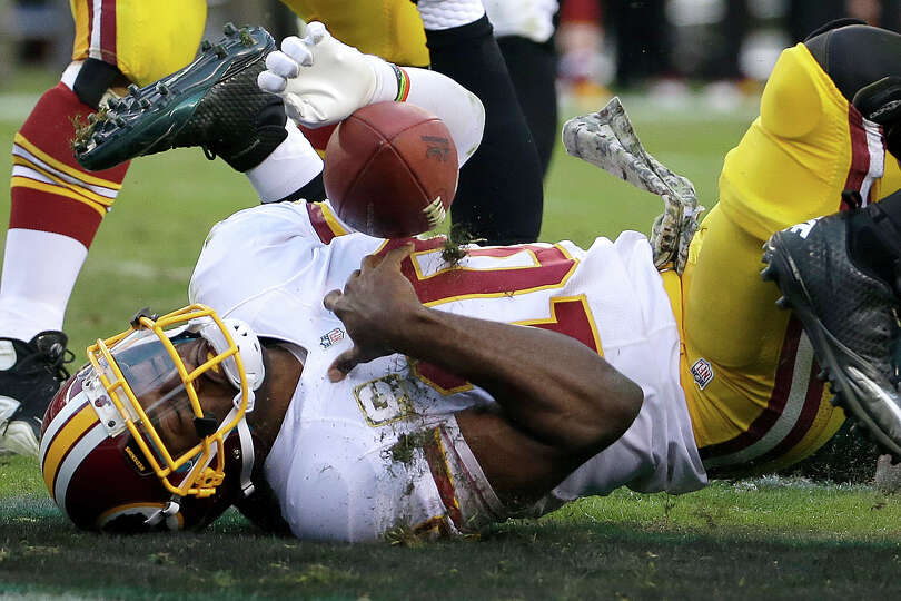 Washington Redskins quarterback Robert Griffin III lands after rolling into the end zone for a two-p