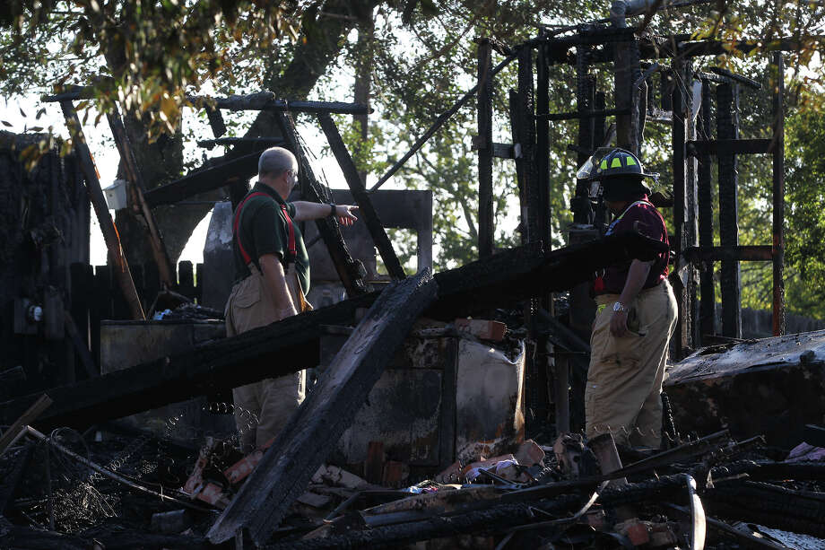 Bexar County fire officials examine a home that burned shortly after 2:00 a.m. Monday November 18, 2013 on the 8100 block of Whistler in Northeast Bexar County. A house next door to this home was also damaged after a gas line between the two homes caught on fire. Neighbor Bonnie Muller said the owner of the home was in Houston at the time of the fire and was just recently notified about the fire. Photo: JOHN DAVENPORT, John Davenport/Express-News / ©San Antonio Express-News/Photo may be sold to the public