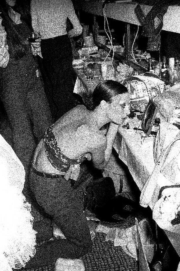 Anjelica Huston applying makeup backstage at a London fashion show, 1973.