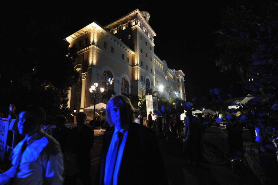 Illuminated by blue police lights, people leave the celebration of the opening of the new Scientology Flag Building on November 16, 2013 in Clearwater, Florida.   Construction of the 377,000-square-foot center began in 1999 and cost more than $40 million dollars to complete.   (Photo by Tim Boyles/Getty Images) Photo: Tim Boyles, Getty Images / 2013 Getty Images