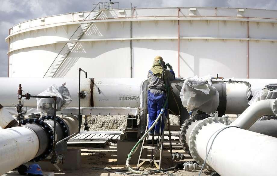 Jose Martinez uses a sand blaster preparing to paint oil pipelines at the new NuStar Terminal in Port Corpus Christi. Photo: Bob Owen, San Antonio Express-News
