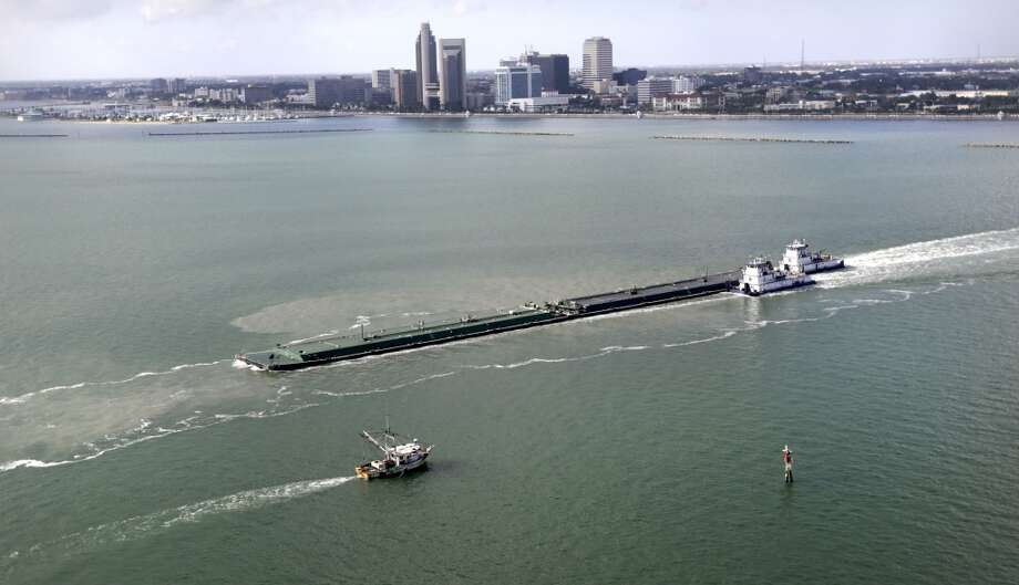 A shrimping boat passes a oil barge after leaving Port Corpus Christi. Photo: Bob Owen, San Antonio Express-News