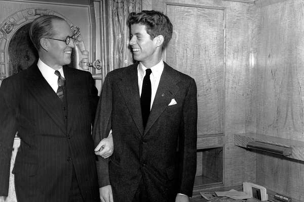 "Joseph P. Kennedy, left, U.S. Ambassador to Great Britain, stands with his son, John F. Kennedy, in New York. Kennedy, was the second son, and one of nine children, of tycoon Joseph P. Kennedy. When first son Joseph Jr. was killed during World War II, Jack became the designated heir. Himself a Navy veteran and survivor of a collision with a Japanese destroyer, he would write to his friend Paul Fay that, once the war was over, ""I'll be back here with Dad trying to parlay a lost PT boat and a bad back into a political advantage."""