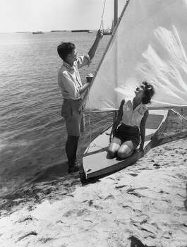 American politician John F Kennedy stands at the water's edge hoisting the sail of a small boat, upon which kneels his wife, Jacqueline Bouvier Kennedy, Hyannis Port, Massachusetts. Photo: Hulton Archive, Getty Images / Archive Photos