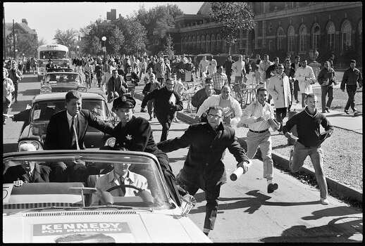 American politician John F. Kennedy rides in a car as supporters run after him after a campaign stop, Illinois, October 1960. Photo: Paul Schutzer, Time & Life Pictures/Getty Image / Time & Life Pictures