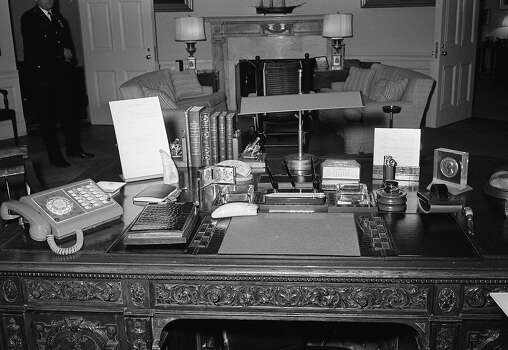 View of the top of President Kennedy's desk in the Oval Office of the White House showing books, telephone and mementos, shown March 9, 1962. Photo: John Rous, AP / AP