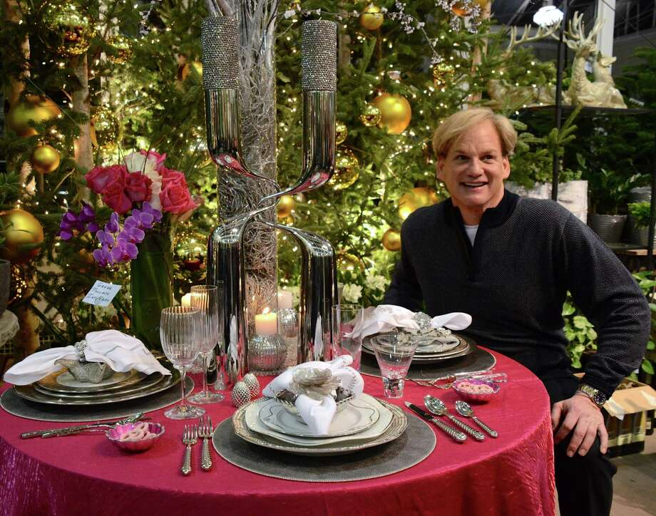 "Designer Greg Pollack enjoys his own table setting and discusses his designs with guests at Nielsen's Florist & Garden Shop's ""Home for the Holidays"" tablescape event, benefiting Darien EMS-Post 53, on Thursday, Nov. 14, 2013. Photo: Jeanna Petersen Shepard / Darien News freelance Jeanna Petersen Shepard"