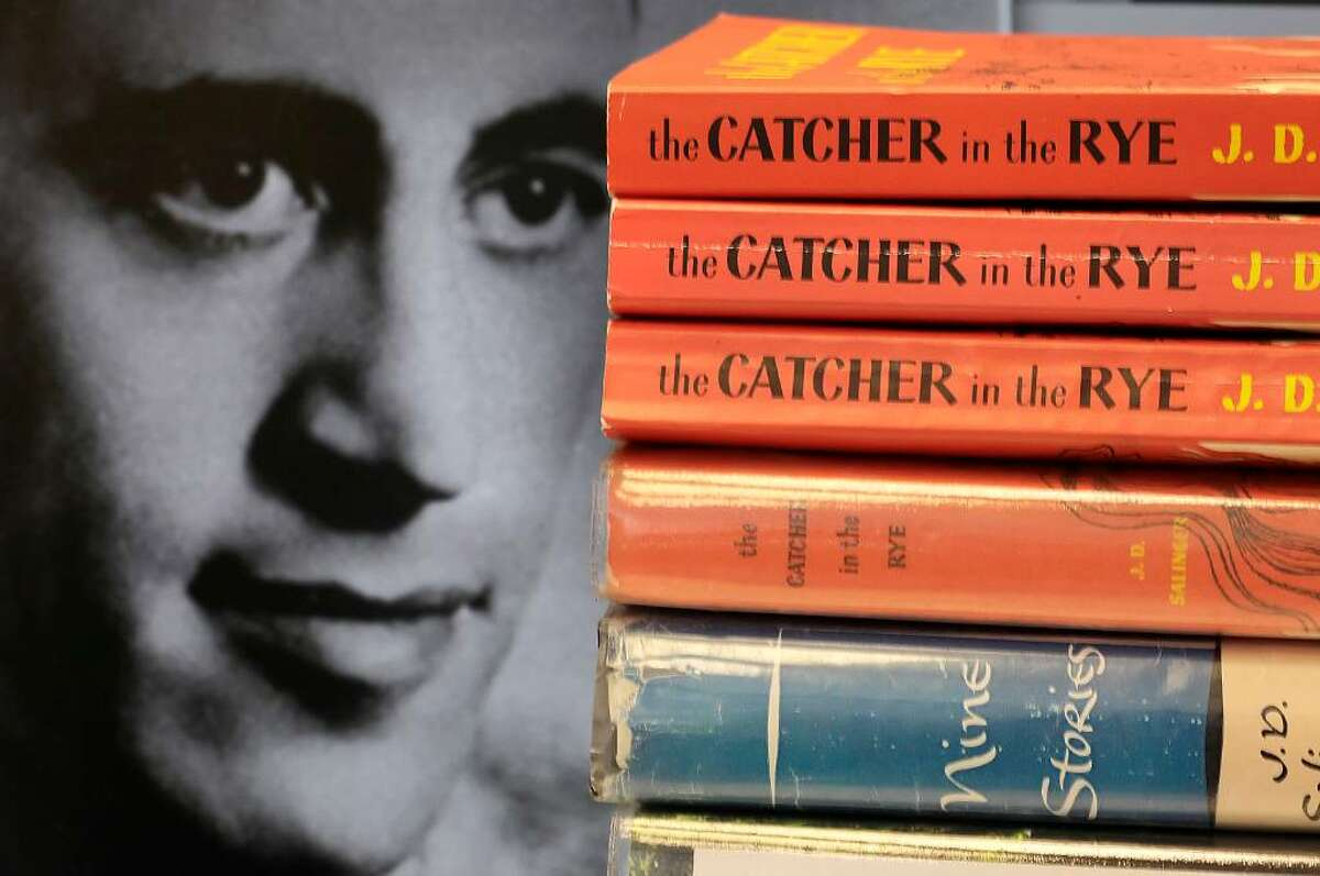"""Copies of J.D. Salinger's classic novel """"The Catcher in the Rye"""" as well as his volume of short stories called """"Nine Stories"""" are seen at the Orange Public Library in Orange Village, Ohio on Thursday, Jan. 28, 2010. Salinger, the legendary author, youth hero and fugitive from fame whose """"The Catcher in the Rye"""" shocked and inspired a world he increasingly shunned, died Wednesday at the age of 91. At left is a 1951 photo of the author. (AP Photo/Amy Sancetta)"""