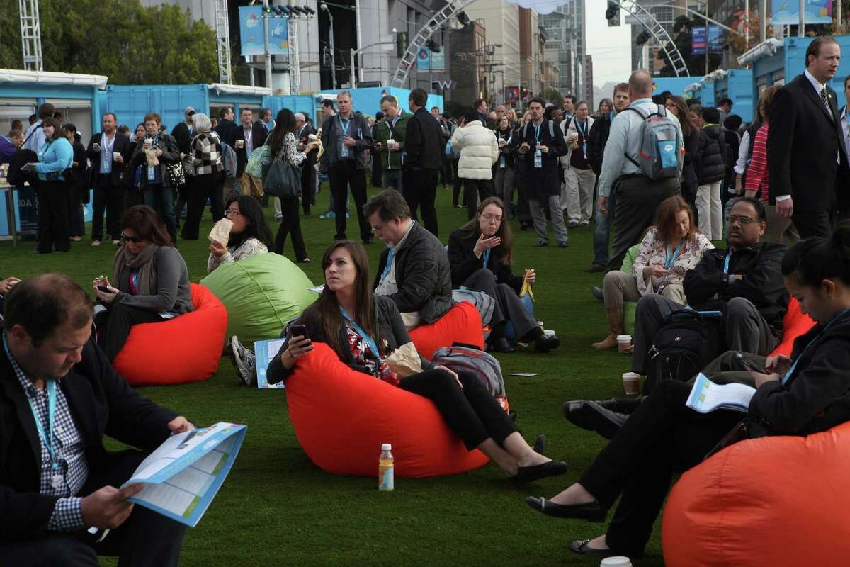 Meaghan Shroyer (center) from J.B. Hunt in Arkansas watches a plaza monitor before the 2013 Dreamforce conference in San Francisco.