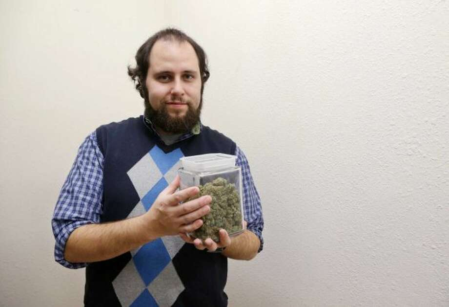 "Yevgeniy ""Eugene"" Frid, general manager of A Greener Today, holds a container of a marijuana strain called Scoobie Doobie ""High CBD"" in Seattle in this photo made Tuesday, Nov. 12, 2013.   It started with small doses that eased the aches of restaurant work. But over time, Frid found himself addicted to prescription painkillers.   ""It completely envelopes your whole life."" He tried to quit many times, and when he finally did, he says, cannabis played a huge role - displacing the opiates with a substance much gentler on the body. Frid, 28, quit his job doing business management and marketing for a video game company when a friend asked him to help start a medical marijuana dispensary.   A Greener Today opened in Seattle in 2012 and now serves about 4,000 people. Frid says his most gratifying work is helping patients get off opiates the way he did, so he has mixed feelings about applying for a recreational retail license. The future of unregulated medical marijuana in Washington is dim _ many state officials see it as a threat to the heavily taxed recreational system.   Some medical dispensary operators believe they have little choice but to convert to the recreational market.   ""We don't know what's happening,"" Frid says. Photo: Elaine Thompson, Associated Press"