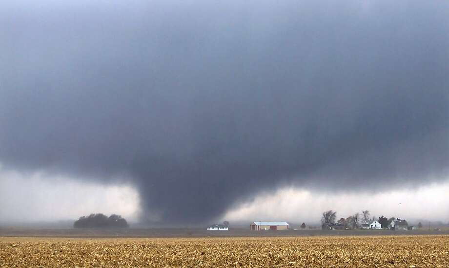 A tornado spins across farmland two miles west of Flatville, Ill. The twister damaged many farm buildings and 