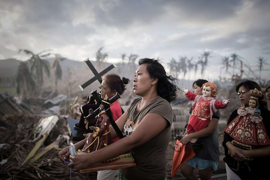 Carrying crosses and figurines, survivors of Super Typhoon Haiyan march during a religious procession in Tolosa on the eastern Philippine 