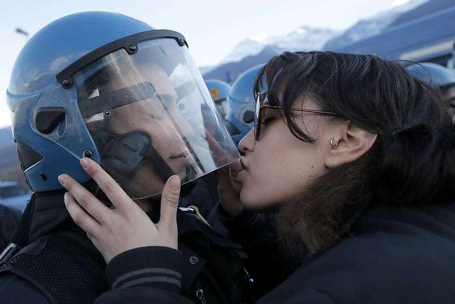 I love the way you suppress dissension: A protester kisses a riot police officer during a rally in Susa, Italy, against a planned 